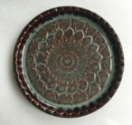 Wine coaster with decorative design and cork padding on bottom.
