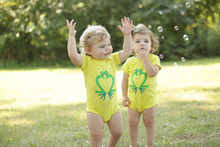 "Our twin ""Friendly Frog"" bodysuit twin set features our Friendly Frog in green ink on a zest bodysuit."
