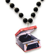 Retro rockabilly record player and black pearl necklace.