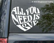 """White custom vinyl decal of a Beatles quote - """"All You Need is Love"""" stylized into a heart shape. By Minglewood Trading.  Applied to the rear window of a minivan"""
