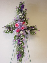 Lavender and Pink Sympathy Cross by Enchanted Florist Pasadena TX - funeral cross of flowers in pinks and lavenders including pink roses, white, lavender, and pink other flowers. Deer Park florist delivers to Deer Park Funeral Directors and Grandview Funeral Home daily.  RM501