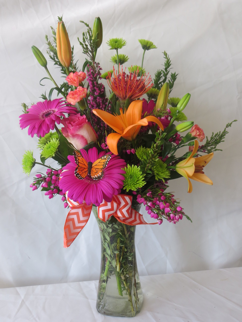 Hot pink flowers with orange lilies with a butterfly in a vase the sherbet and chevron orange lily arrangement with butterfly hot pink and orange flowers in reviewsmspy