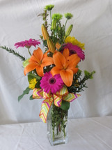 Cheerful Chevron Hot Pink Gerbera Bouquet by Enchanted Florist Pasadena TX. Bright hot pink and orange flowers in a clear glass vase with a chevron print ribbon. Send flowers online now in Houston TX, Pasadena TX, Deer Park TX, Webster TX and surrounding areas. RM154