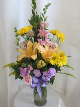 The Lavender Blossom Lily Snapdragon Flower Bouquet by Enchanted Florist Pasadena TX. A beautiful pastel flower bouquet with peach lilies, yellow daisies, and pink spray roses in a clear glass vase. Send happy birthday flowers the same day in Houston TX. RM158