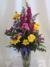 Purple People Pleaser Flower Bouquet with Yellow Roses and Gerberas by Enchanted Florist Pasadena TX. Bright yellows and pleasing purple flowers in a clear glass vase. Flowers include yellow roses and purple carnations. RM162