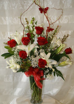 Butterfly Memories White Lilies and Red Roses by Enchanted Florist Pasadena TX. Red roses and white lilies in a clear vase with curly willow and red butterfly. Same day flowers in Houston TX.  RM513