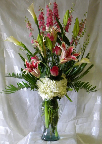 Beautiful Bounty Stargazer Vase Bouquet by Enchanted Florist for a Houston TX flower delivery. Pink roses, fragrant stargazer lilies, white hydrangeas, pink larkspur, calla lilies and other flowers in Marilyn Monroe clear vase for same day delivery in Houston TX and surrounding areas. Call for Houston flower delivery (832)850-7677 RM514