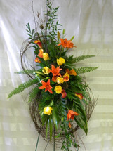 Autumn Harvest Grapevine Wreath by Enchanted Florist TX. Sympathy flowers include orange lilies, yellow roses, and orange mini calla lilies with tropical foliages arranged on this grapevine wreath. Funeral home flowers in Houston TX. RM519
