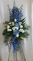 The Ocean Blue Funeral Spray by Enchanted Florist Pasadena TX is a beautiful blue and white sympathy standing spray of flowers.  It includes blue delphinium, blue hydrangeas, white lilies and white roses with accent foliages. RM544