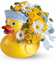 Ducky Delight Baby Boy Flowers by Enchanted Florist Pasadena TX. This adorable yellow ducky is iconic among new baby decor. A yellow ceramic duck with matching hat for a new baby Boy is complete with precious white daisies, yellow spray roses, and buttons. RM175
