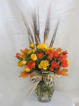 Fall Simply Spray Rose Bouquet by Enchanted Florist Pasadena TX. Our fall bouquet of yellow and orange spray roses in a clear vase with wheat accents and fall leaves perfect for a side table or desk. We offer same day delivery on fall flowers for delivery in Pasadena TX and surrounding areas. RM186