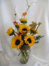 Sassy Sunflower Bouquet by Enchanted Florist Pasadena TX.  Seasonal bright sunflowers with branches and fall leaves expertly designed in a clear vase accented with copper glitter decor and river rocks inside the vase for that earthy feel. RM183