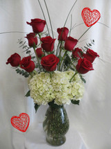 Impress Her Dozen Roses for Valentines Day from Enchanted Florist Pasadena TX. Our Premium option when sending one dozen roses. It includes our upgraded Bella vase, white hydrangeas, dozen premium red Ecuadorian roses, eucalyptus, and bear grass for the flowy look. RM918