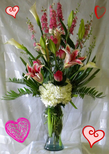 Romantic Rendezvous for Valentines Day by Enchanted Florist Pasadena TX. A romantic bouquet of large calla lilies, fragrant pink stargazer lilies, pink roses, white hydrangeas and more. In our large Marilyn Monroe vase, it's a spectacular and show stopping bouquet for Valentines Day for you main girl! RM933