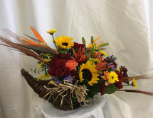 Thanksgiving Cornucopia Centerpiece from Enchanted Florist Pasadena TX. Cornucopia's are an iconic part of our Thanksgiving traditions so why not incorporate them into our centerpiece flowers. This beautiful bouquet includes sunflowers, birds of paradise, red mini roses, lilies, wheat and more. RM209
