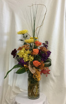 Papaya Fall Orchid Bouquet from Enchanted Florist in Pasadena TX. A lovely tropical bouquet of flowers styled in a contemporary cylinder vase includes a cymbidium orchid, roses, stock and would work well in an office or as a buffet piece. Flower delivered in La Porte TX RM111