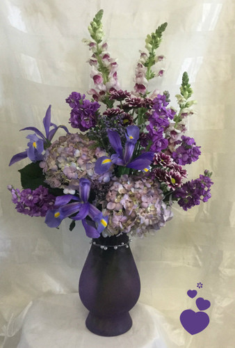 Purple Rain Mothers Day Flowers by Enchanted Florist Pasadena TX is a stunning purple bouquet of iris, hydrangeas, snapdragons and stock in our exclusive pearl wrapped violet frost vase. This all purple bouquet of flowers will tickle any purple lover's fancy and delight your mom on her special Mother's Day. RM804