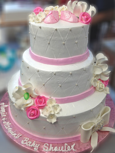 """Approximate Servings 80. Sizes: 7"""", 10"""" & 14"""". Sugar flowers, sugar baby showed and sugar bow adorn this pearled three tiered cake."""