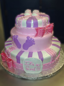 "Approximate Servings 80. Sizes: 7"", 10"" & 14"". Three tiered baby feet decorated cake accented with sugar bows and baby booties."