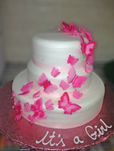 "Approximate Servings 80. Sizes: 7"", 10"" & 14"". Three tiered cake with ribbon wrapping around and cascading sugar butterflies."