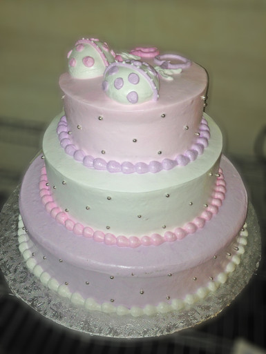 """Approximate Servings 80. Sizes: 7"""", 10"""" & 14"""". Three tiered rattle topped cake with silver NON EDIBLE pearls all around."""