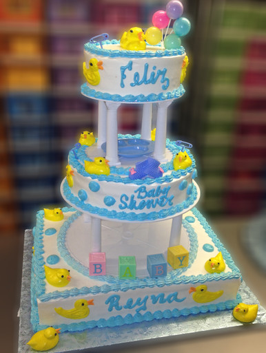 "Approximate Servings 90. Sizes: 7"", 10"" & 1/2 Sheet. Yellow duckies accent this cake at every angle as a special addition baby blocks and baby booties are included to make this a spectacular choice for your special day."