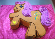 Approximate Servings 50. Size: Custom. Cake is cut out in the shap of a Cartoon Pony.