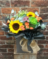 A handtied aquapac bouquet made up of a selection of vibrant Autumnal shades.
