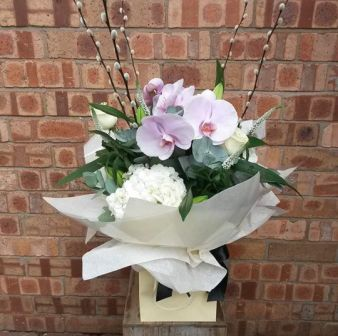 A stunning handtied aqupack bouquet. Statement Phalanopsis orchids arranged with pure white lillies, roses, hydrangea, veronica, pussy willow and fragrant eucalyptus.