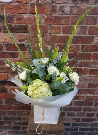 A simply elegant handtied aqua packed bouquet of white and green flowers. Tall and striking, this bouquet features Lillies, Roses, Gladioli, Hydrangea, Lissianthus, Steel grass and Eucalyptus.  Beautifully arranged, packaged and presented.