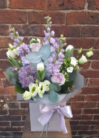 A handtied aquapac bouquet made up of a selection of seasonal flowers. Image shown represents the Grand option.