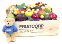 A Hand crafted wooden Gift box filled with Fresh seasonal Fruit, Baci and Ferrero Rocher Chocolates, including a Cute soft and cuddly Message Bear that is wearing a Happy Birthday blue jumper.