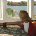 Woman cleaning window with green microfiber glass cleaning towel.