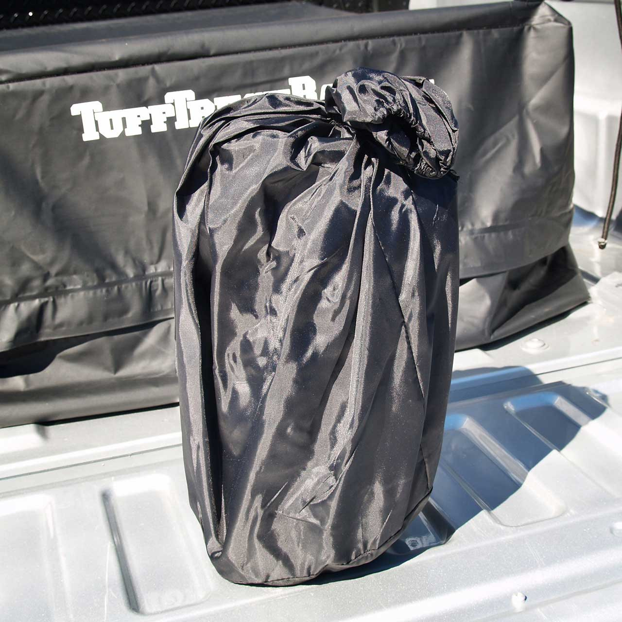 Black waterproof Tuff Truck Bag inside of the included stow bag, ready for storage when not in use