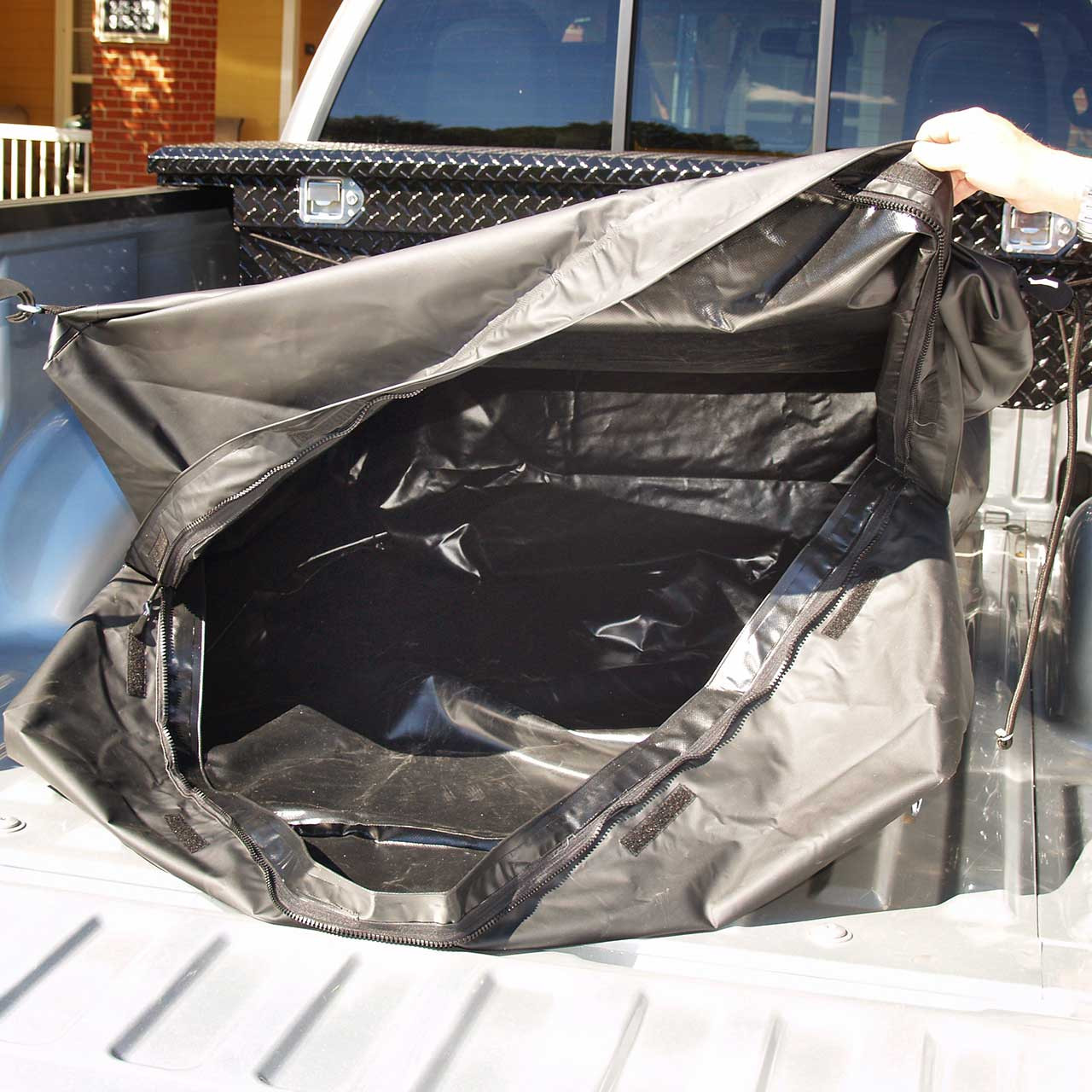 Open waterproof black Tuff Truck Bag so the viewer can see how large the inside area of the bag for keeping cargo and luggage dry and safe