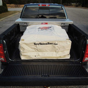 Khaki waterproof Tuff Truck Bag full of cargo in the back of a pickup truck bed