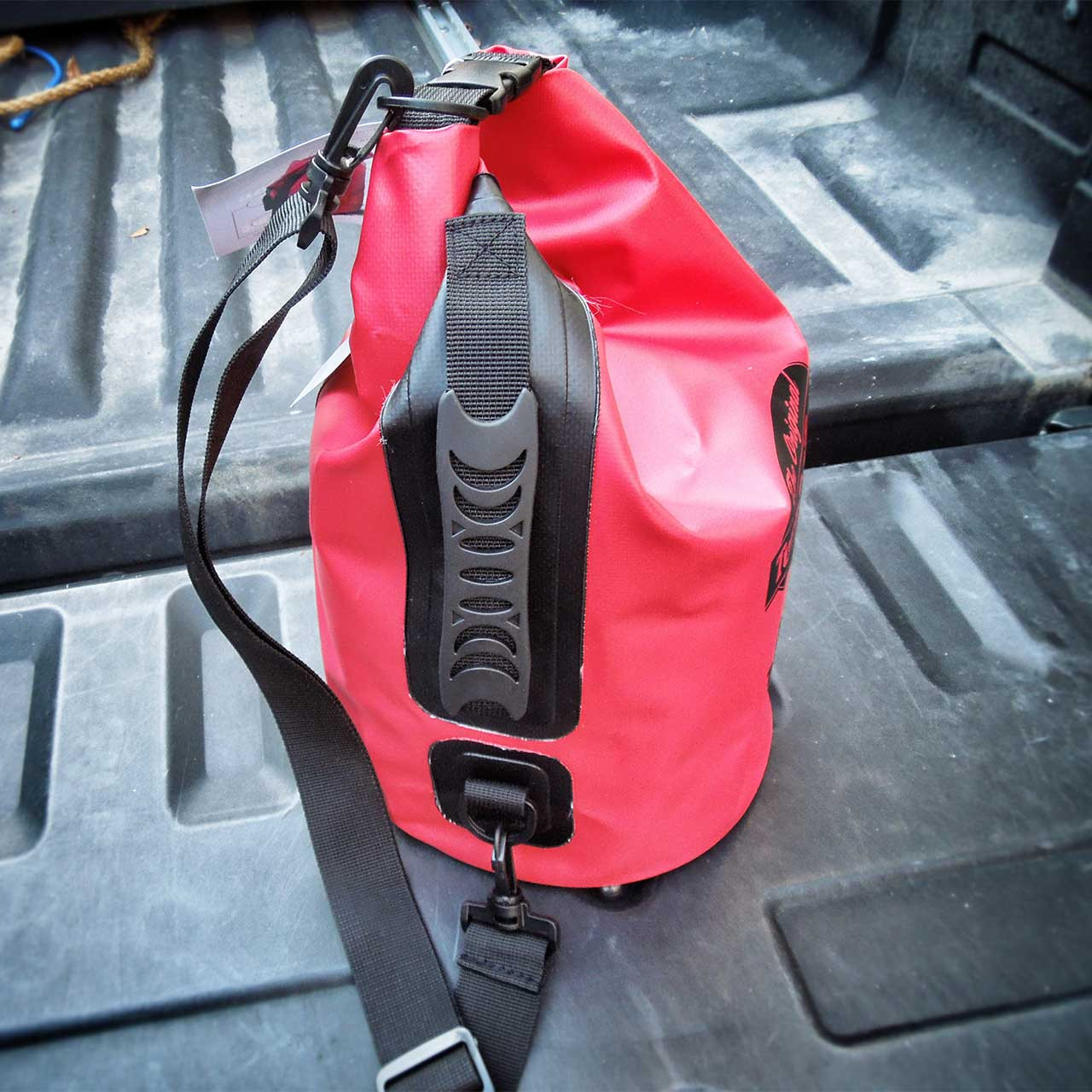 Back handle view of the waterproof class three red bag with strap and roll down handle.