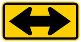 yellow and black sign, rectangular shape, arrow pointing two directions.