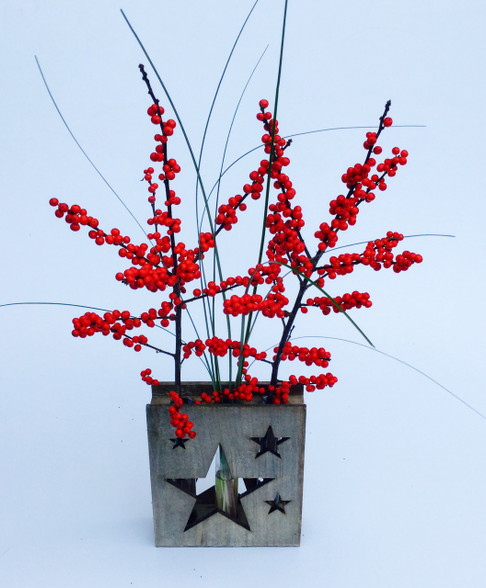 A lovely wooden star  vase with three glass tubes filled with berries and grass.