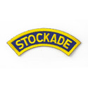 "This blue curved patch with a yellow border features the word ""STOCKADE"" in yellow and is used on the shoulder of the Stockade uniform shirt."