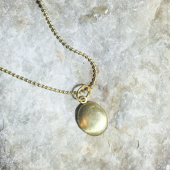 tiny brass breast milk locket.
