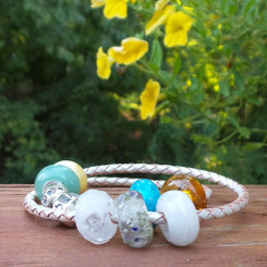 Milk beads shown with accent beads and a memorial flower bead.