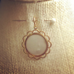scalloped circle breast milk pendant.