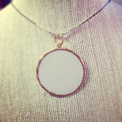 large brass breast milk pendant.
