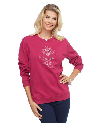 Woman in magenta pullover sweater with bird applique