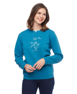 Woman in teal pullover sweater with blue birds applique