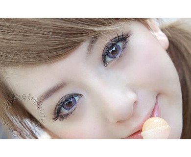 Natural yet vibrant Barbie Puffy Violet circle lenses on model's brown eyes.