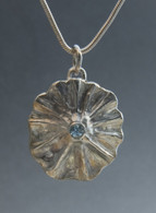 Sterling silver shell pendant with blue topaz,  on a 16-inch sterling snake chain