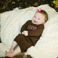 Monogrammed brown baby gown in the Caboodle font with hot pink thread.