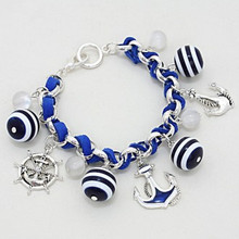 "• Style No : [231534] CB110973-AS-BL-1 1/4""H  • Color : Russian Silver / Blue / Clear  • Size : 1 1/4"" H, 8"" L  • Nautical Anchor/ Helm  • Striped Weaved Sea Life Charm Bangle Bracelet"